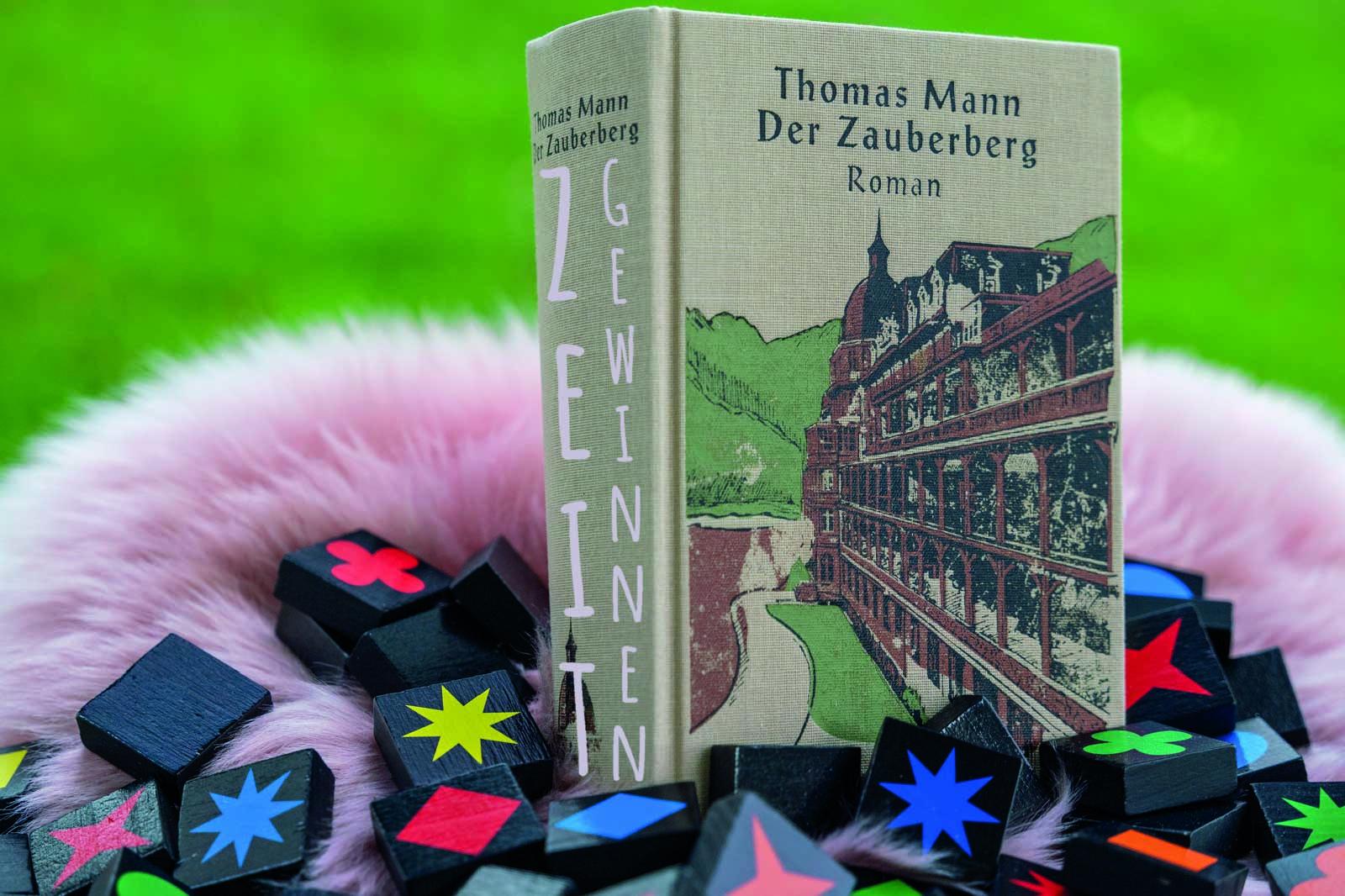 Das Buch Zauberberg von Thomas Mann umrahmt von Spielsteinen mit der Bildaufschrift: Zeit Gewinnen